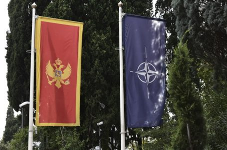 In this photo taken Monday, Nov. 11, 2019, the Montenegro, left, and NATO flags wave in front of the Montenegrin Defense Ministry in Podgorica, Montenegro.Deployed inside the sprawling communist-era army command headquarters in Montenegro's capital, a group of elite U.S. military cyber experts are plotting strategy in a fight against potential Russian and other cyberattacks ahead of the 2020 American and Montenegrin elections.  (AP Photo/Risto Bozovic)
